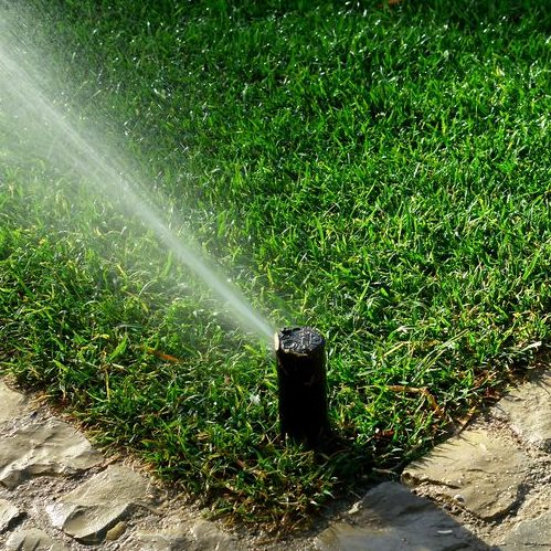 A Picture of an Irrigation System Watering Lawn.